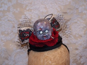"Mama's Boy Hat/fascinator with horror doll head, red velvet flower, ""mama"" frames ribbon bow and netting"